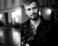 Young male photographer stands on city street in evening. In background there are night city lights. Black and white image. Self-portrait royalty free stock photos