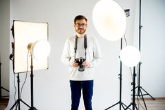 Young male photographer in studio. With professional lighting equipment stock photography