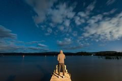 Young male photographer taking photo on jetty by the lake at nig. Ht time. Stargazing photography in New Zealand Royalty Free Stock Photos