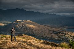 Young male photographer taking photo of scenery in Queenstown. Young male photographer taking photo in photographing posture with mountain scenery during golden Royalty Free Stock Images