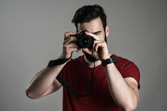 Young male photographer taking picture with digital slr camera. While focusing lens over gray studio background Stock Photo
