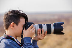 Young male photographer with telephoto Royalty Free Stock Photos