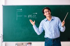 The young male physic standing in front of the green board stock photo