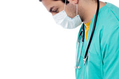 Young male physician wearing surgical mask. Doctor's face covered with a surgical mask Royalty Free Stock Photo