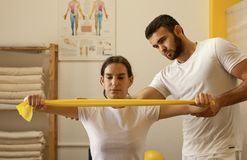 Physiotherapists practicing with resistance band. Young male physiotherapist training with colleague. Practice with yellow resistance band. White uniforms Royalty Free Stock Photography