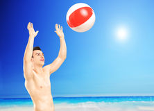 Young male playing with a beach ball, next to a sea. Young man playing with a beach ball, next to a sea Royalty Free Stock Images