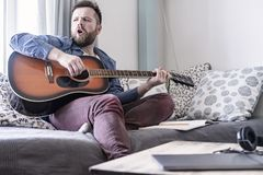 Male plays an acoustic guitar and sings a song of his own composition sitting on a sofa in a comfortable home environment in. A young male plays an acoustic stock images