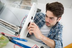 Young male plumber examining electric heater. Young royalty free stock photos