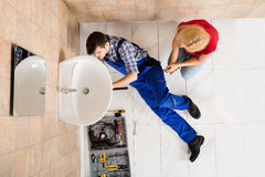 Young Male Plumber Fixing Sink In Bathroom Stock Images