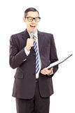Young male presenter holding microphone and clipboard Royalty Free Stock Images