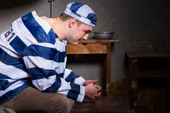 Young male prisoner wearing prison uniform has lost in thought w Stock Images