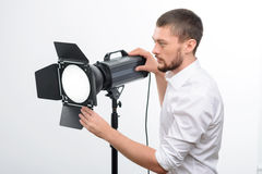 Young male professional photographer is busy. Spotlight assembling. Young good-looking male photographer is busy fixing the spotlight stock photo