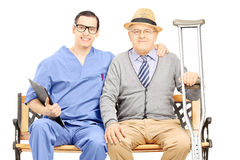 Young male professional posing with elderly gentleman seated on Royalty Free Stock Images