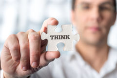 Young male professor holding puzzle piece with word Think in a c Stock Images