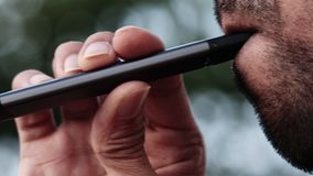 Young male puffs on a vape pen device few drags. Young male with beard puffs on a vape pen device few drags outdoors, extreme close up stock video footage