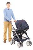 Young male pushing a baby stroller Royalty Free Stock Photos