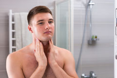 Young male put some aftershave lotion on a face by two hands sta Royalty Free Stock Photos