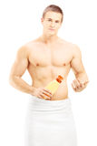 Young male putting on body lotion after bath Royalty Free Stock Photography