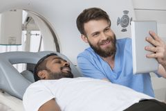 Radiologist Showing Digital Tablet To Patient Lying On CT Scanne Royalty Free Stock Photo