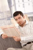 Young male reading bad news from newspaper Stock Photography