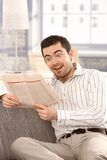 Young male reading good news at home smiling Royalty Free Stock Image