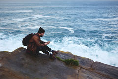 Young male reading text message on cell telephone while sitting on a rock near sea with waves. Man traveler watching world map via app on mobile phone while Stock Images