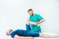 Young male receiving massage from therapist. A chiropractor stretching his patient`s legs in medical office. Neurological physica. L examination. Osteopathy royalty free stock image