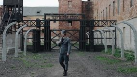 A young handsome male actor dressed as a German soldier walks towards camera. The reconstruction of a concentration camp. A young male reenactor dressed as a stock footage