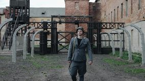 A young handsome male actor dressed as a German soldier walks towards camera. The reconstruction of a concentration camp. A young male reenactor dressed as a stock video