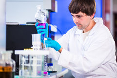 Young male researcher carrying out scientific research in a lab. (shallow DOF; color toned image Stock Image