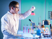 Young male researcher holding a flask. Side view of male scientist in a chemistry laboratory holding a flask with colorful fluid, making a discovery Stock Images