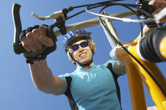 Young Male Riding Bicycle. Low angle view of a happy young male riding bicycle against blue sky stock image