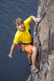 Young male rock climber hanging over the water. Making his next difficult move. Serious, manful face Royalty Free Stock Images