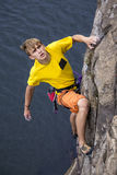 Young male rock climber hanging over the water Royalty Free Stock Photo