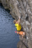 Young male rock climber hanging over the water and. Making his next difficult move. Serious, manful face Stock Image