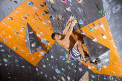 Young male rock climber in indoor climbing gym. Young male rock climber on challenging route in indoor climbing gym Royalty Free Stock Photography