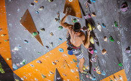 Young male rock climber in indoor climbing gym. Young male rock climber on challenging route in indoor climbing gym Stock Photo