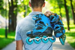 Young male roller skater holding inline roller skates. Royalty Free Stock Photos
