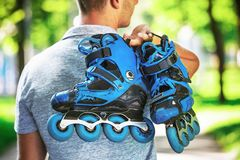 Young male roller skater holding inline roller skates. Royalty Free Stock Image