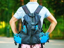 Young male roller skater with roller backpack - shoot from behin Royalty Free Stock Photography