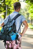 Young male roller skater with roller backpack - shoot from behin Royalty Free Stock Images