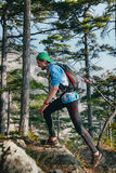 Young male runner with a backpack runs down rocks in mountain Stock Images