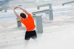Young male runner do physical exercises in the fresh air in summer day. Back view of sportsmen dressed in orange t-shirt with copy space for your brand Stock Photo
