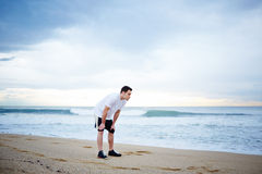 Young male runner dressed in the white t-shirt rest standing on the beach on beautiful sea background. Morning jog, fitnes and healthily lifestyle, sport and stock images