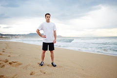 Young male runner dressed in the white t-shirt standing on the sand resting after intensive morning jog. Morning jog, fitnes and healthily lifestyle, sport and stock image