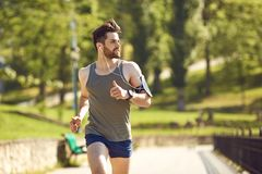 A young male runner jogs in the park.  stock images