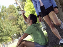 Young male runner pouring water over head by woman resting against tree Stock Photo