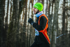 Young male runner running through forest. Ekaterinburg, Russia - November 14, 2015: young male runner running through woods in cold weather. frost on his Royalty Free Stock Photo