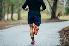 Young male runner running on road. In Park during marathon. feet in a spray of dirt Stock Photography