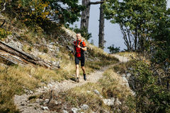 Young male runner running with walking sticks Royalty Free Stock Photography